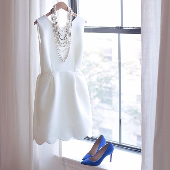 a sleek sleeveless mini dress with a scallop edge, layered necklaces and blue shoes for something blue