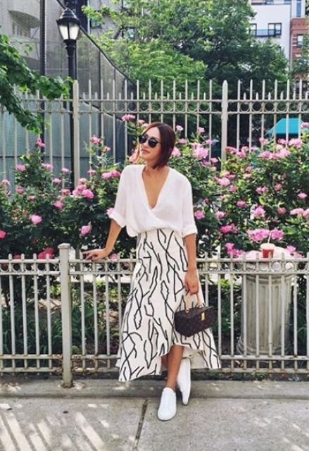 a white button down with cuffed sleeves, a printed midi skirt, whiet sneakers and a catchy bag