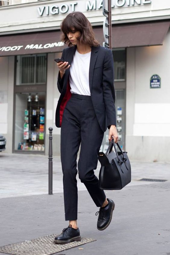 a black pantsuit with an oversized jacket, a white tee and flat shoes for a Parisian chic feel