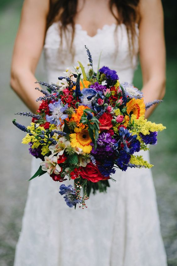 a wildflower wedding bouquet with red, yellow, orange, purple, lavender and greenery for a bold look