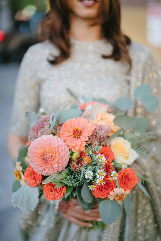 a peach and coral wedding bouquet with dahlias, roses and muted greenery