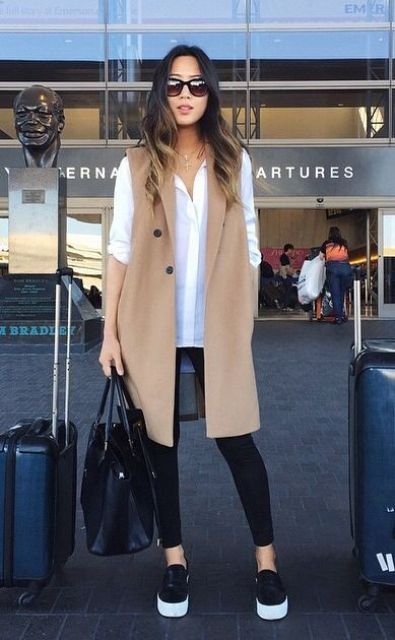 black leggings, a white shirt, black slipons, a tan long vest and a large black bag for a casual feel
