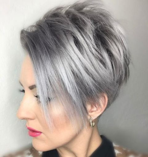 a pixie bob wiht long side bangs in trendy grey hair color looks chic