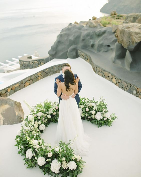 a chic and lush wedding altar with greenery and white blooms on high roof on Santorini for a wow look