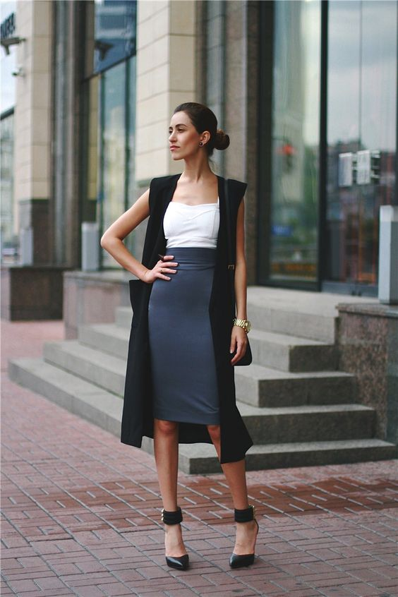 a grey midi knee pencil skirt, a white top, a long black vest and black ankle stap shoes