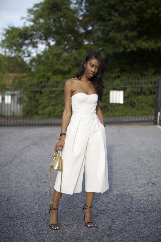 a white strapless jumpsuit with culottes, black lace up heels and a metallic small bag