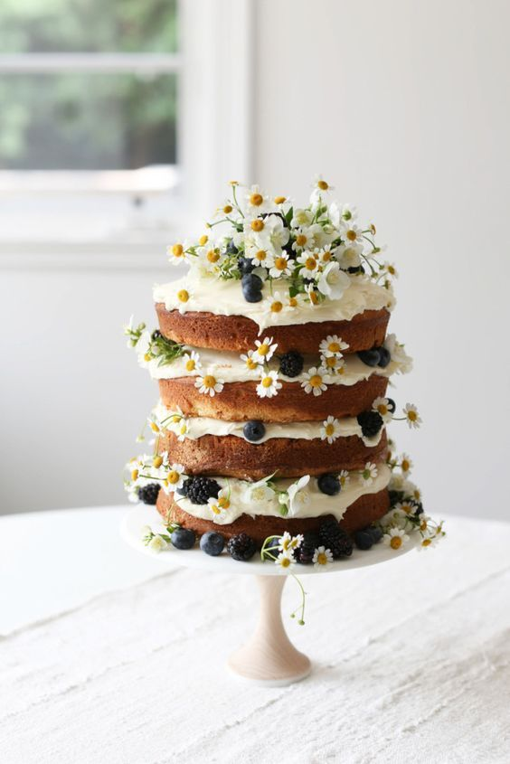 a vanilla naked layer cake with blackberries, blueberries and daisies for a summer garden shower
