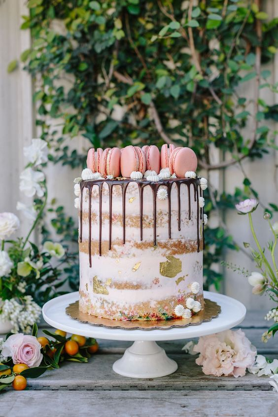 a semi-naked cake with gold foil and topped with pink macarons on top plus small meringues