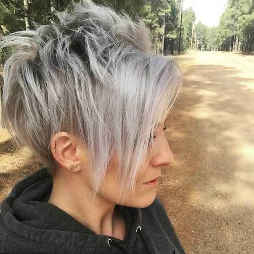a longer pixie haircut with bangs with trendy grey balayage looks daring and cool