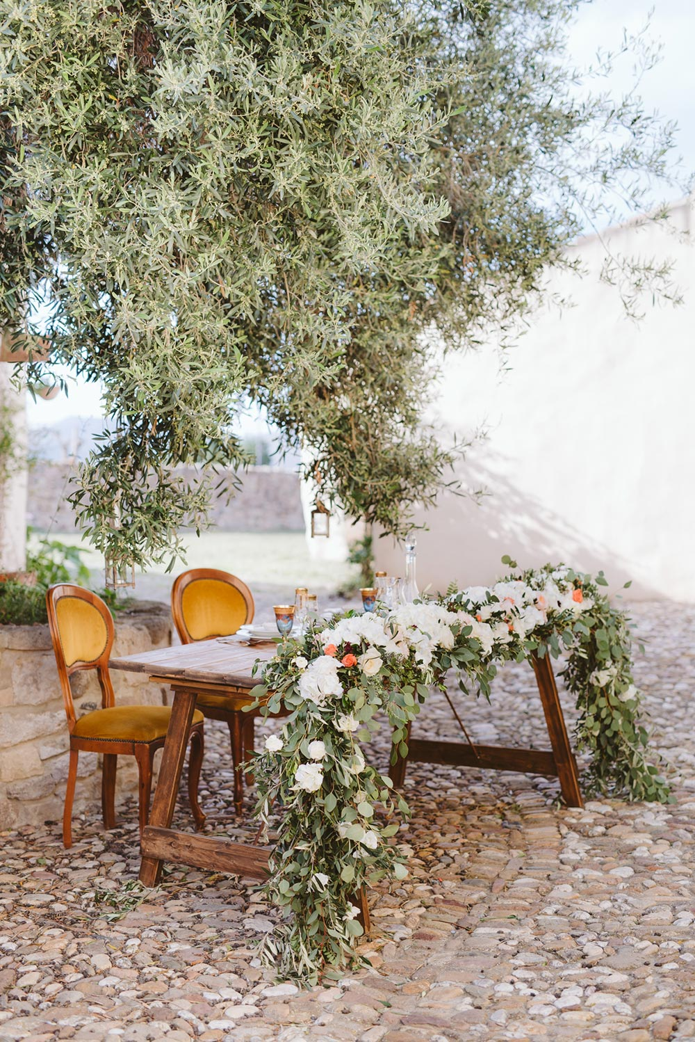 overgrown floral garland and mustard velvet chairs sweetheart table