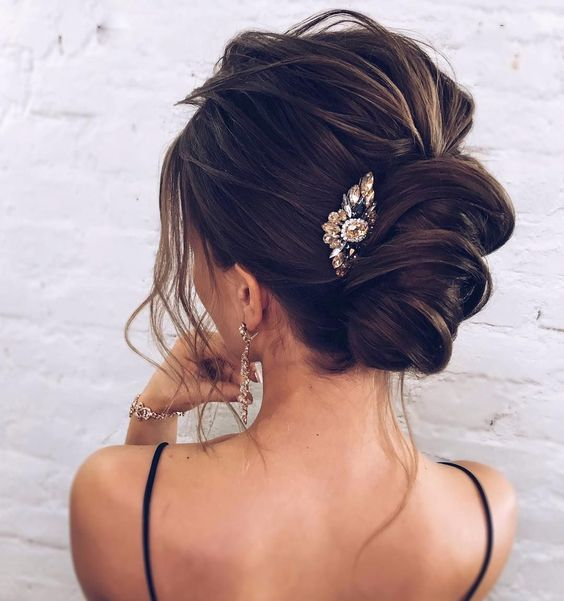 a gorgeous messy chignon with messy volume on top, locks down and a bold rhinestone hairpiece