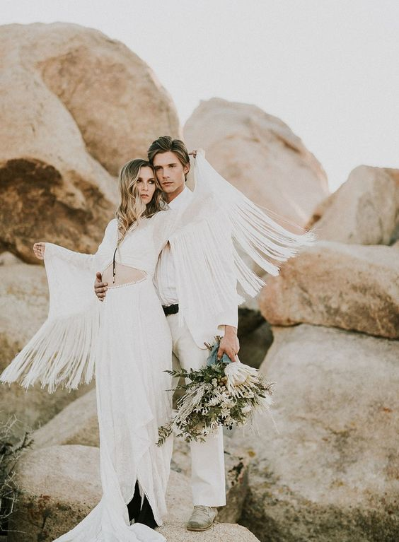 a unique wedding dress with a cutout, a front slit, a long train and long fringed sleeves