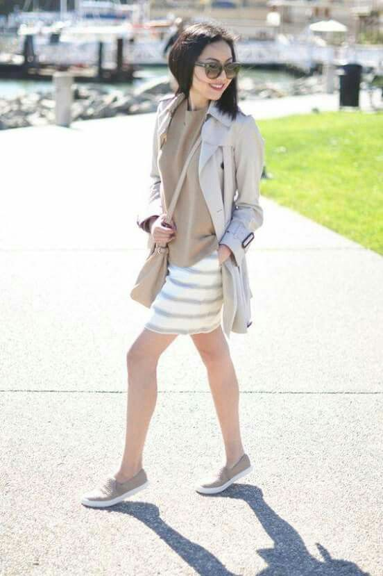 a tan top, a striped skirt, a grey trench, grey slipons and a tan bag for a girlish feel