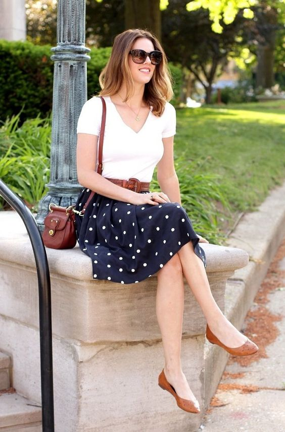 a white t-shirt, a navy polka dot skirt, brown flats and a matching bag for a retro-inspired look