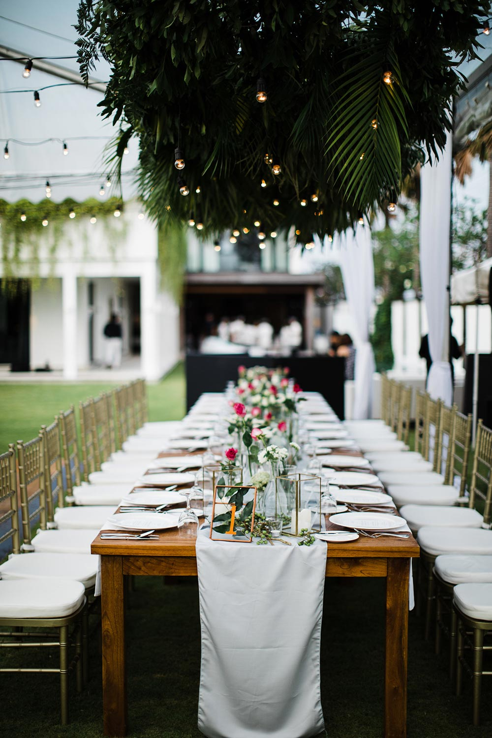 tropical wedding reception tablescape with palm frond ceiling