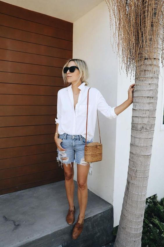 a white shirt, ripped blue denim shorts, a brown bag and perforated brown flats for a summer look