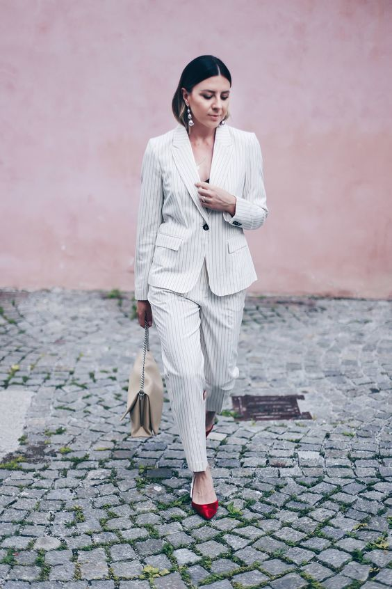 a white thin stripe pantsuit with a black top underneath, a neutral bag and red kitten heels