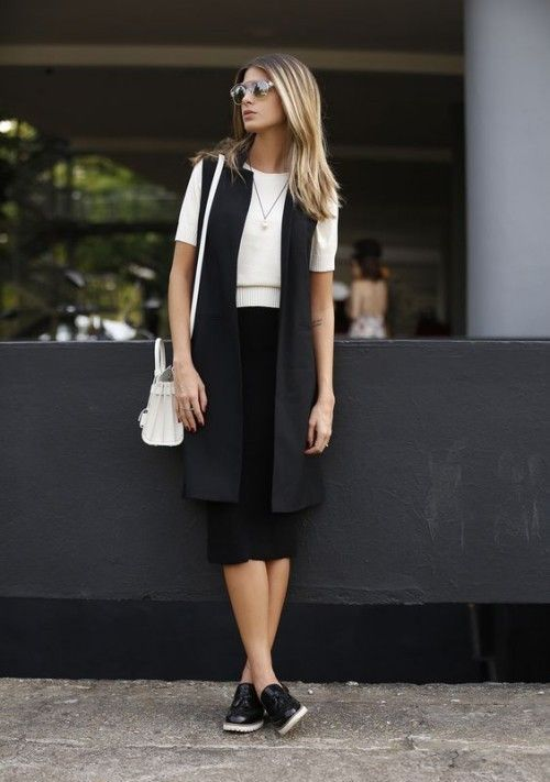 a black midi skirt, a white tee, a black long vest and flat shoes for a minimalist look