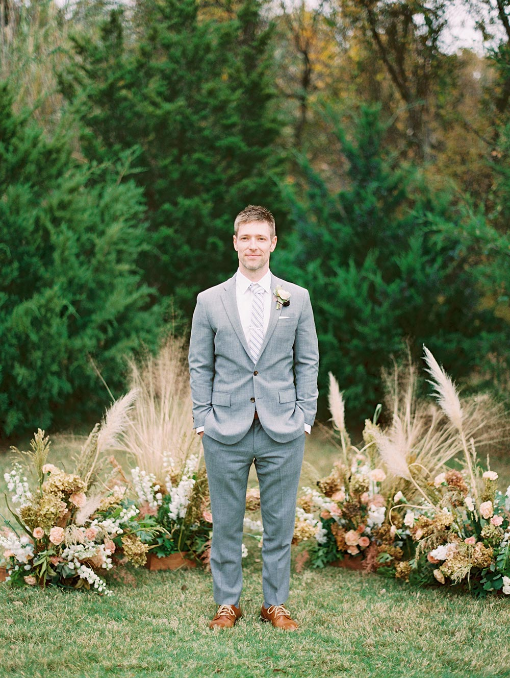 gray groom suit and pampas grass backdrop