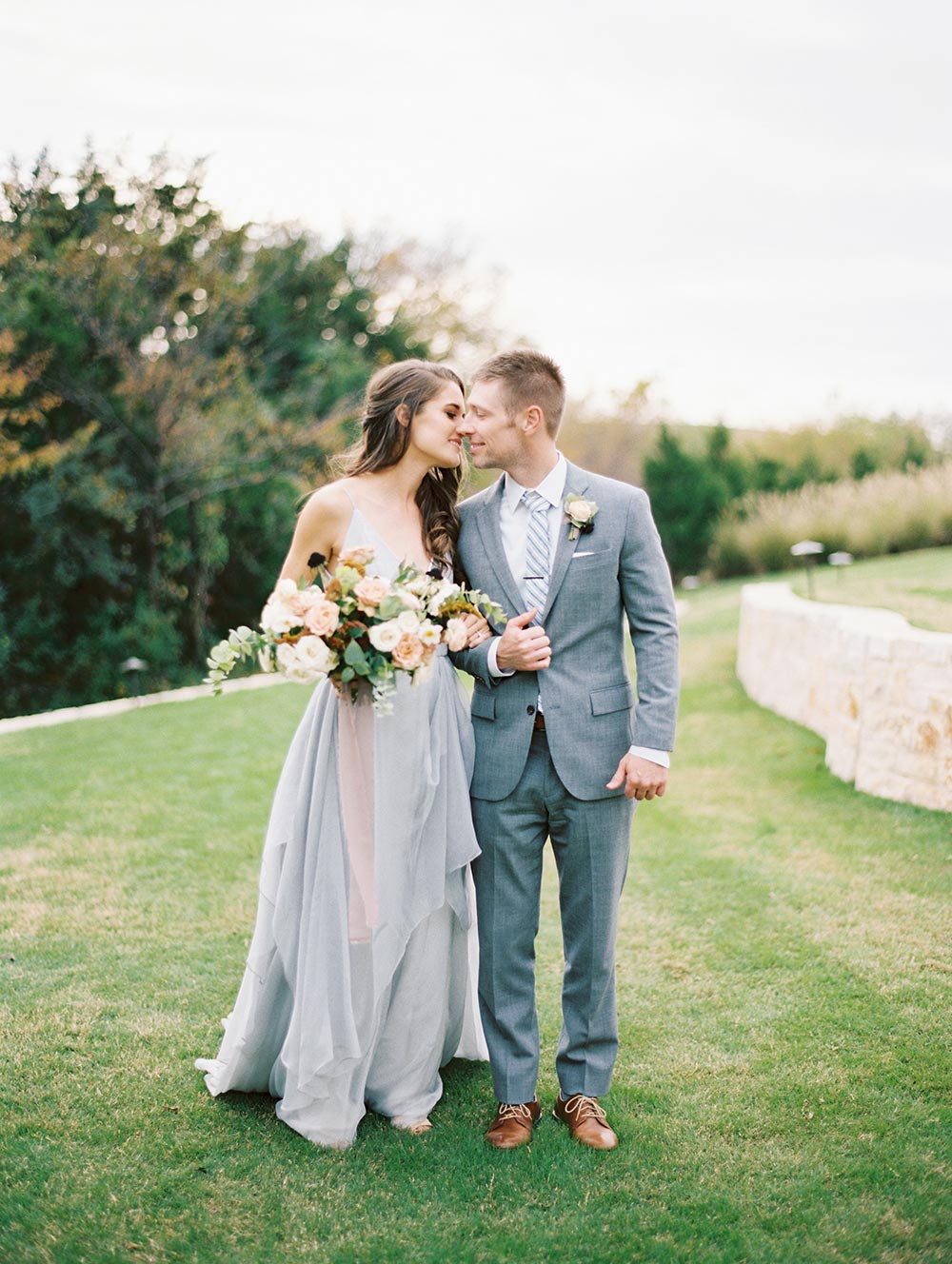 surprise Dallas proposal with dusty blue wedding dress and overgrown flowers