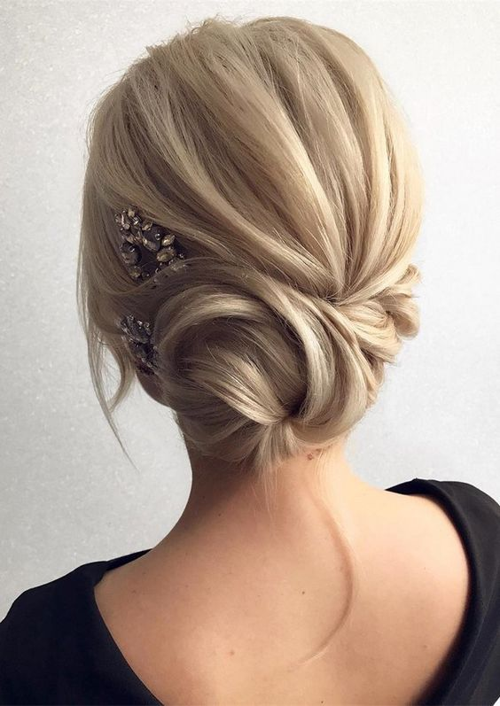 a side twisted low bun with some locks down and a rhinestone hairpiece on one side