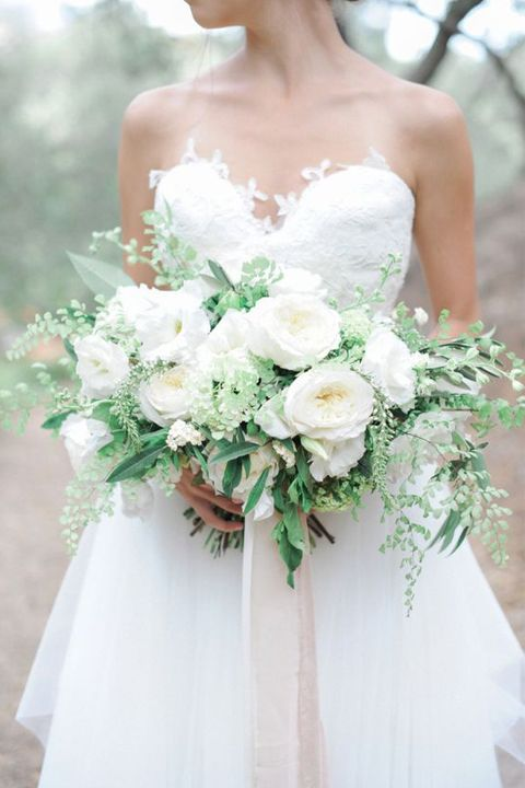 a lush all-white wedding bouquet with greenery and neutral ribbons hanging down is a timeless option