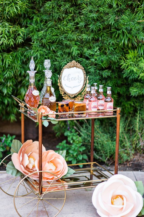 an elegant bar cart with oversized paper flowers and lots of drink served looks very refined and chic