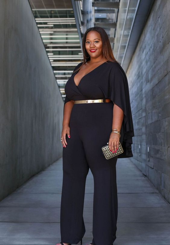 a chic black jumpsuit with a deep V-neckline, cape-like sleeves and a metallic belt