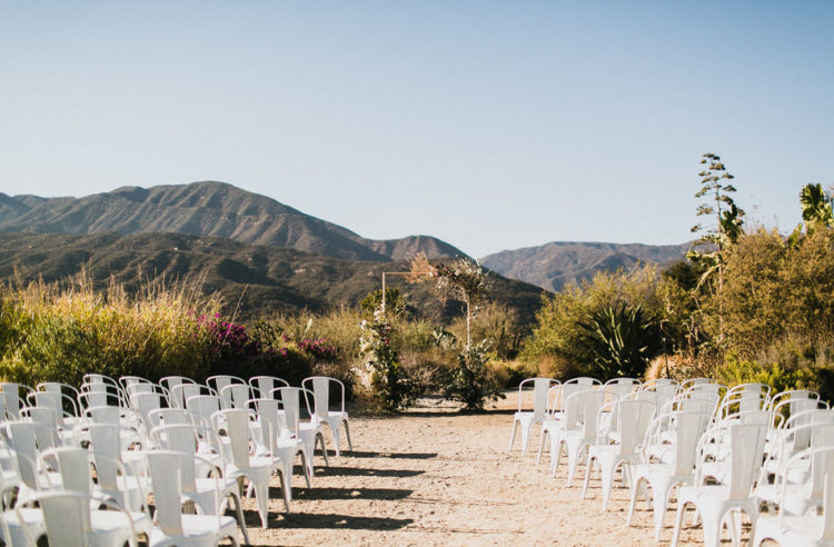 The wedding ceremony space was done with a boho textural arch and white chairs