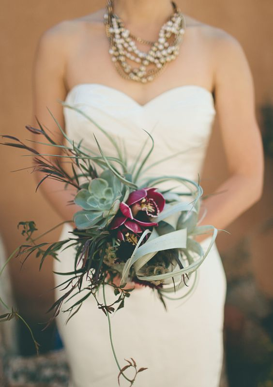 a gorgeous wedding bouquet with an air plant, a succulent, herbs and fuchsia blooms for a statement
