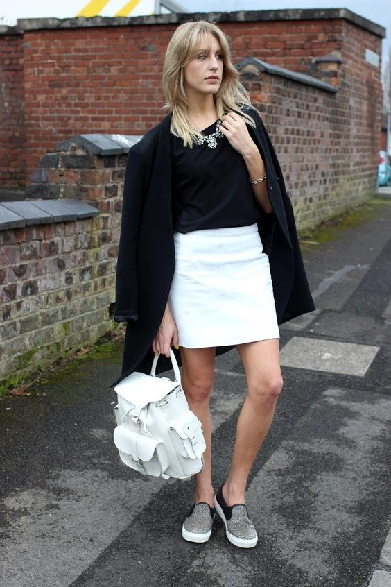 a white skirt, a black top, a long black blazer, a statement necklace, grey slipons and a white backpack
