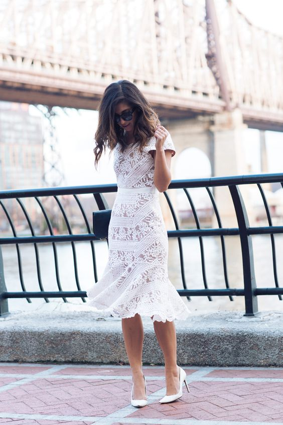 a fitting white lace midi dress with short sleeves and a ruffled skirt, white shoes and a black clutch