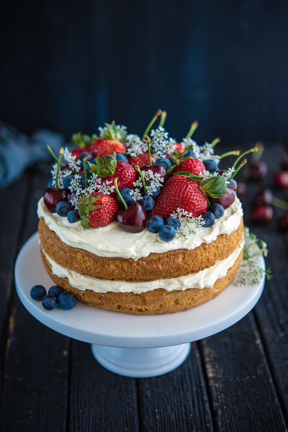 a sponge naked wedding cake with whipped cream, fresh flowers and berries - serve several ones for the guests