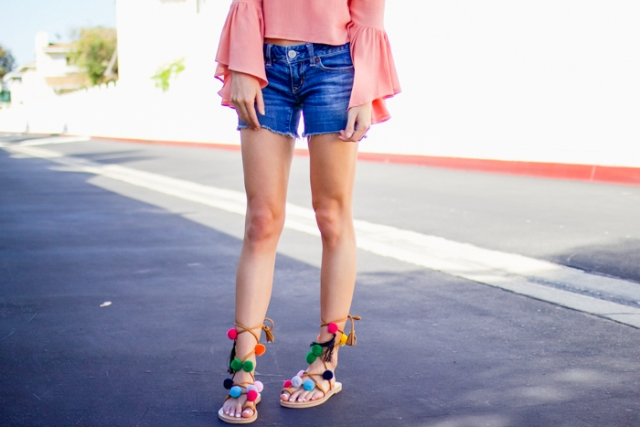 With pink ruffled blouse and denim shorts