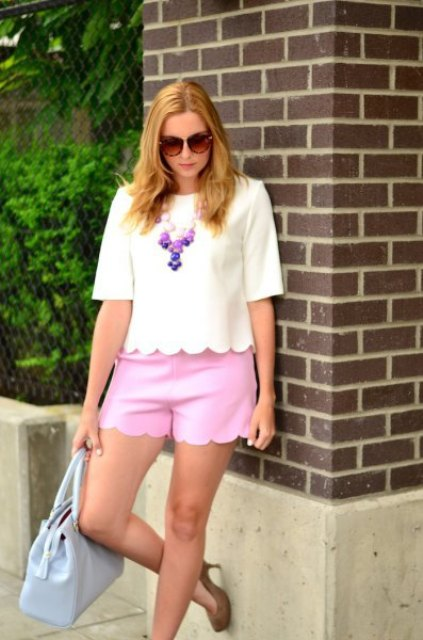 With pink shorts, beige pumps and light blue bag
