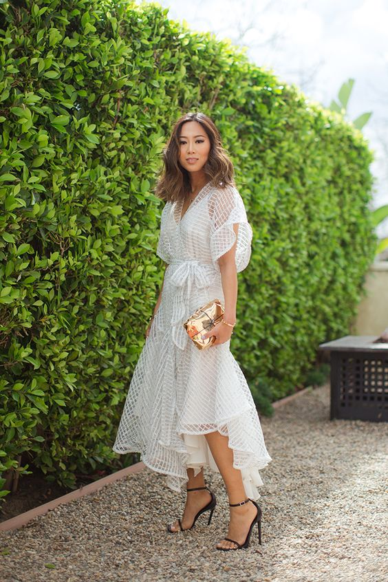 an airy sheer wrap dress over a slip one with much texture and a V-neckline, black heels and a small clutch