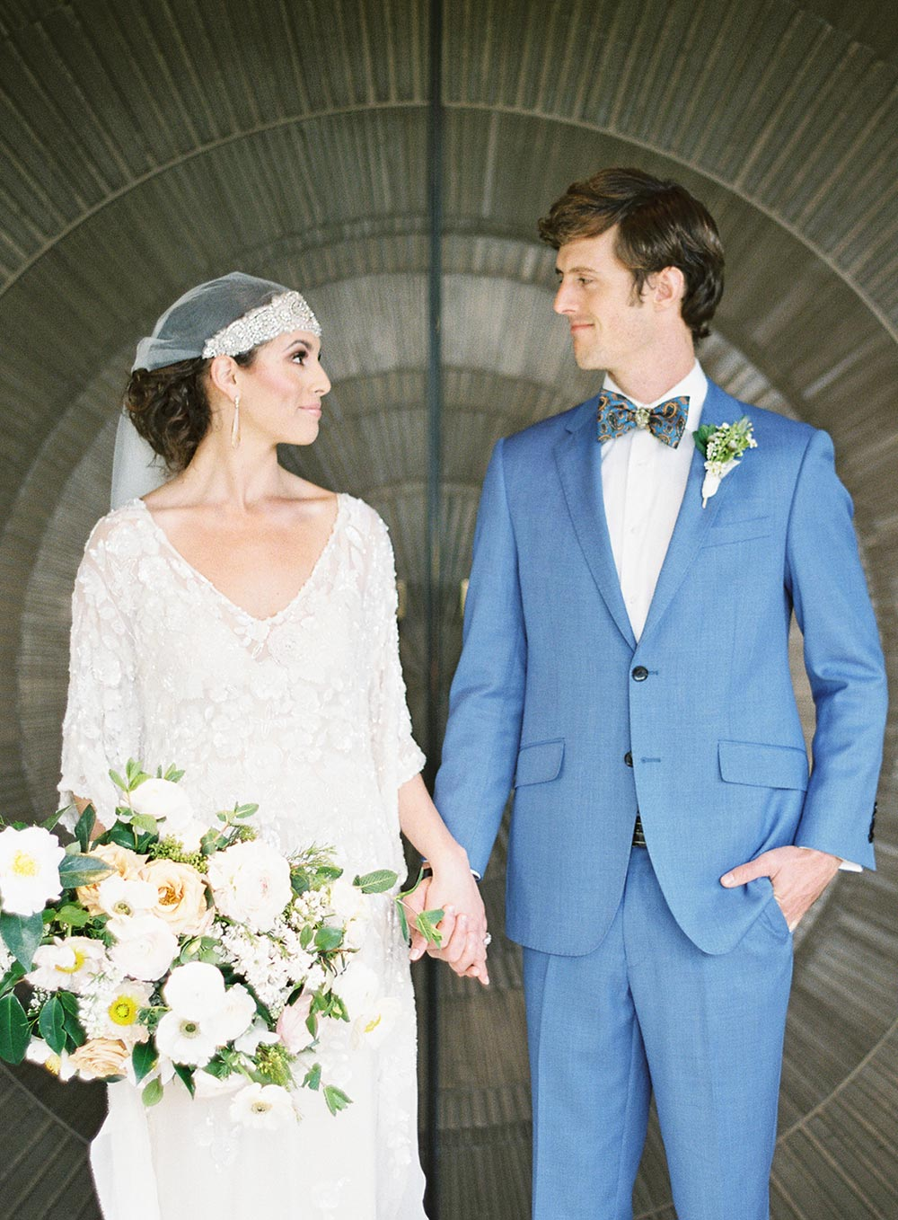 hand beaded caftan wedding dress with boho beaded veil and blue groom suit