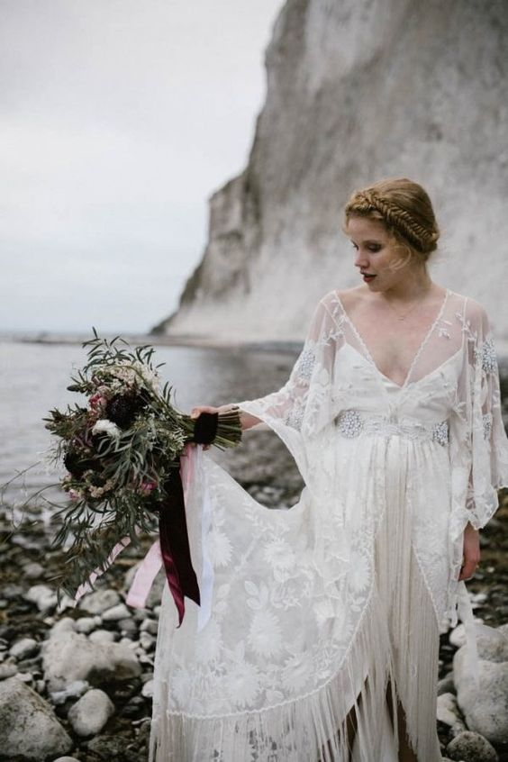 an illusion neckline wedding dress with embellishments, bell sleeves and a fringed front slit skirt