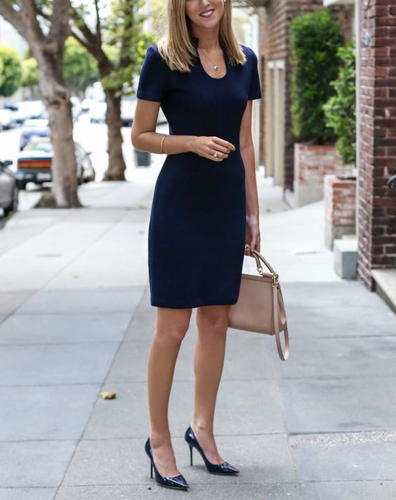 a perfectly fitting navy dress with a cutout neckline, short sleeves and pumps, a nude bag