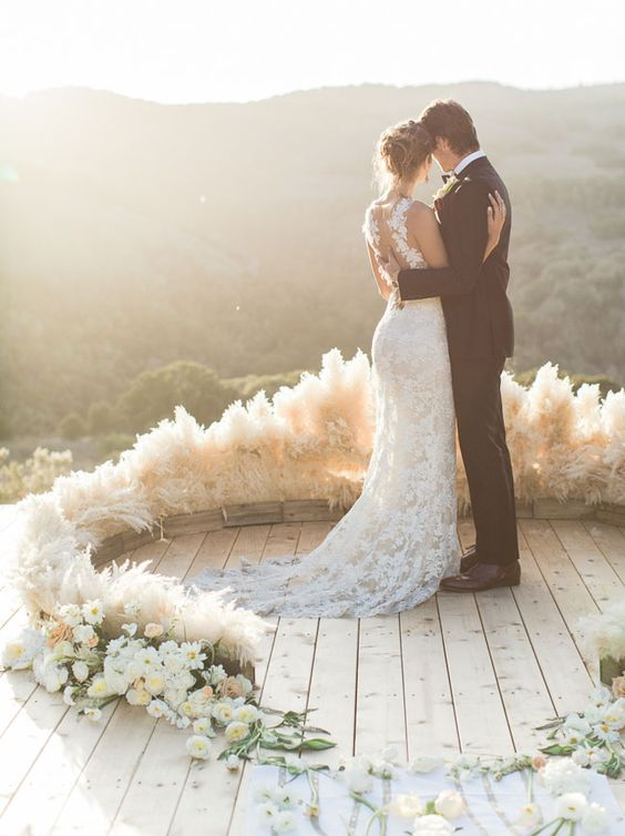 a chic semi circular wedding arch of pampas grass and some white blooms for a textural look
