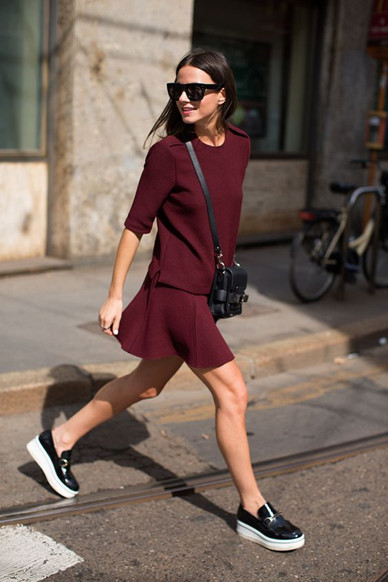 black slipons and a burgundy suit of a skirt and a top plus a black bag for a non-boring look