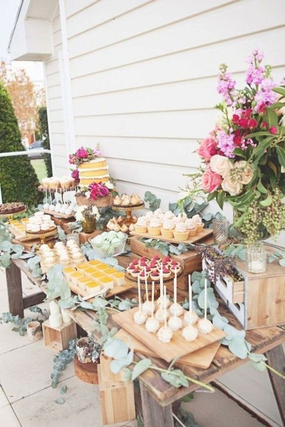 a garden shower sweets table with lush florals and greenery, much eucalyptus makes the table feel fresh