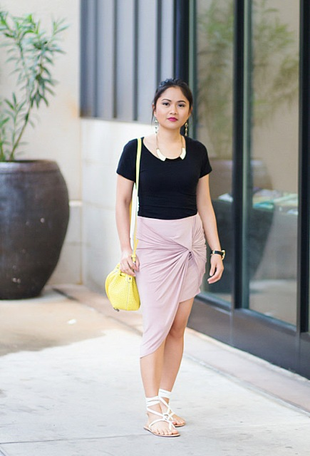 With black t-shirt, pale pink wrap skirt and yellow bag