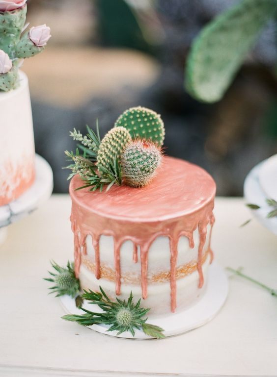 a semi-naked wedding cake with copper drip, thistles and cacti on top for a desert or boho wedding