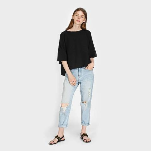 With black loose shirt and distressed jeans