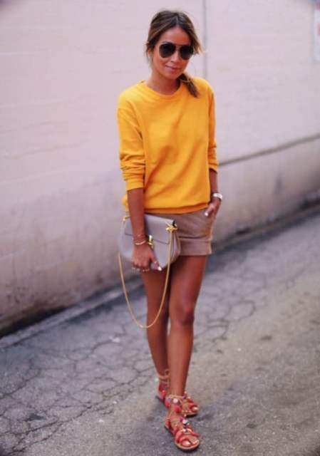 With yellow sweatshirt, beige shorts and beige clutch