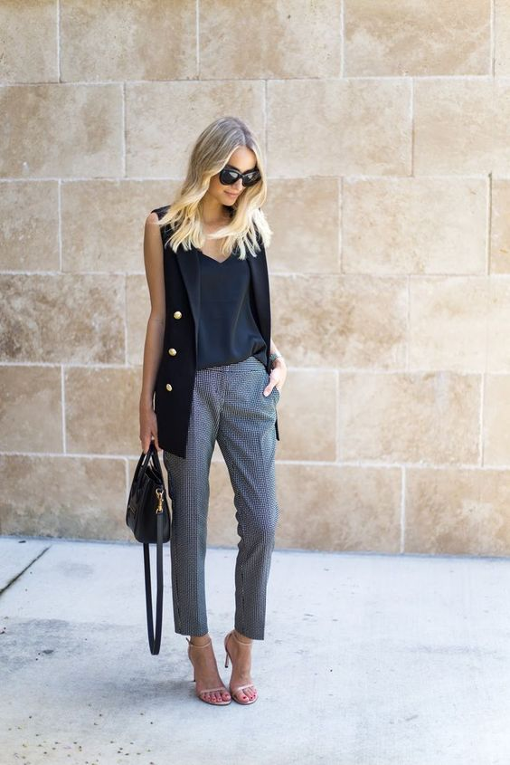 a black top, grey gingham pants, a black long vest, heeled sandals and a bag