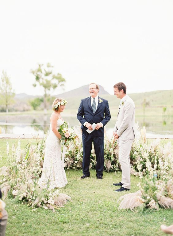 a grass and pastel bloom semicircular wedding altar looks soft and catchy
