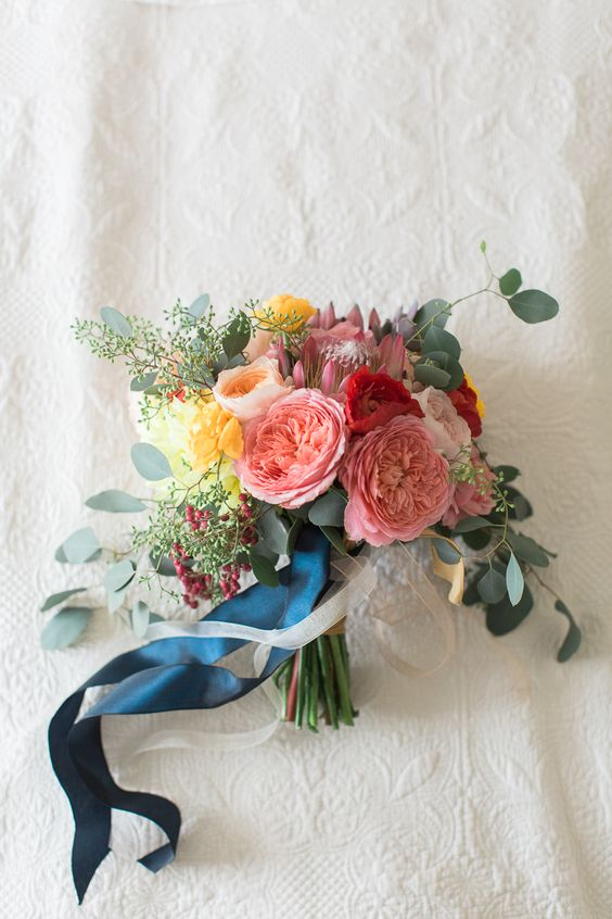 a bright bouquet in pink, yellow, red with eucalyptus and navy ribbons for a colorful summer wedding