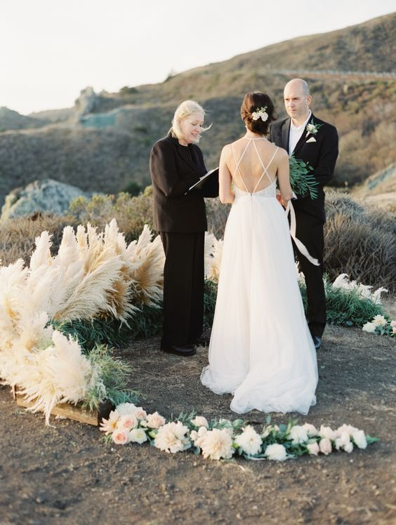 an amazing semicircular wedding altar with some blooms, greenery and pampas grass on a coast
